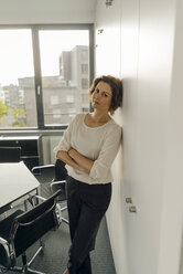 Businesswoman leaning against wall in office, with arms crossed - KNSF04571
