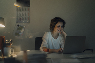 Businesswoman working overtime, using laptop - KNSF04574