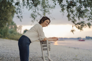 Woman leaning on a chair at the river, watching sunset - KNSF04580
