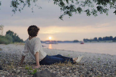 Woman sitting at the river, watching sunset - KNSF04583