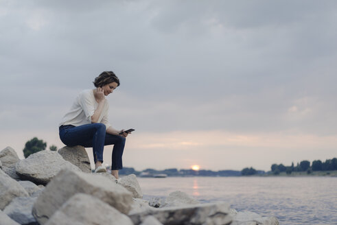 Woman sitting at the river, using smartphone - KNSF04586