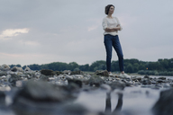 Woman standing at the river at dusk - KNSF04592