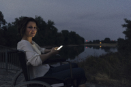 Disabled woman sitting in wheelchair, using smartphone - KNSF04595