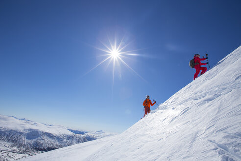 Two skiers are standing on a snowy mountain near the ski resort of Myrkdalen in Fjord, Norway. The sun is shining bright in the blue sky. - AURF02240