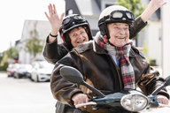 Happy senior couple having fun, riding motor scooter and waving - UUF14920