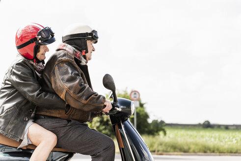 Happy senior couple riding motor scooter - UUF14923