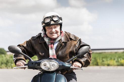Active senior man speeding on his motor scooter - UUF14926