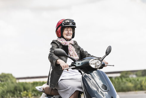 Active senior lady riding motor scooter on the road - UUF14929
