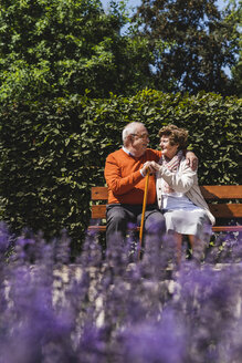 Senior couple sitting on bench in a park, falling in love - UUF14935