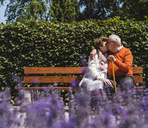 Senior couple sitting on bench in a park, kissing - UUF14938