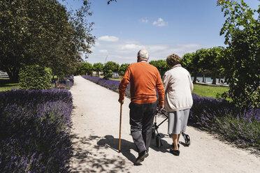 Senior couple walking in park, woman using wheeled walker - UUF14947