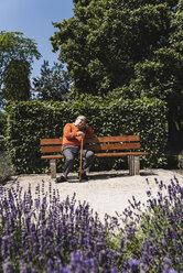 Senior man sitting on park bench, waiting - UUF14950