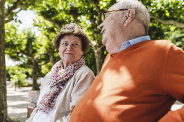 Happy senior couple sitting in park, woman wearing crown - UUF14953