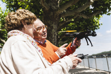 Senior couple playing with a drone in park - UUF14956