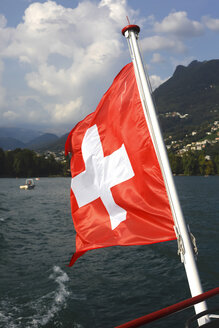 Switzerland, blowing Swiss flag of boat on Lake Lugano, close-up - JTF01051