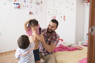 Happy father dressing his children in home bedrom - JASF01913
