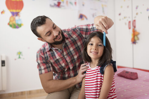 Portrait of smiling girl being combed by her father at home - JASF01919