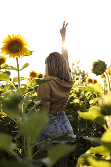 Young woman standing in a sunflower field making victory hand sign - ACPF00295