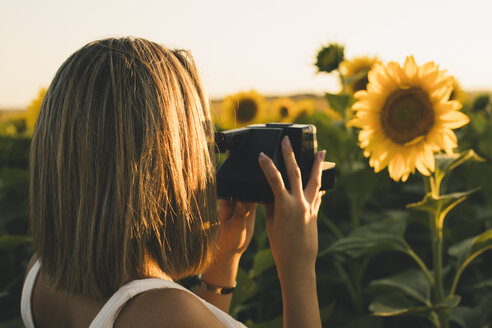 Rear view of woman in a field taking a picture of a sunflower with an instant camera - ACPF00307