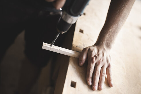 Close-up of carpenter using drill on piece of wood in workshop - PSIF00050
