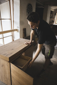Carpenter in workshop testing chest of drawers - PSIF00053