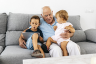 Portrait of grandfather spending time with his grandson and granddaughter at home - JRFF01800
