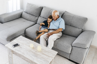 Grandfather and grandson sitting together on the couch at home looking at digital tablet - JRFF01806