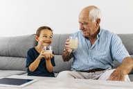 Grandfather and grandson sitting together on couch drinking lemonade - JRFF01809