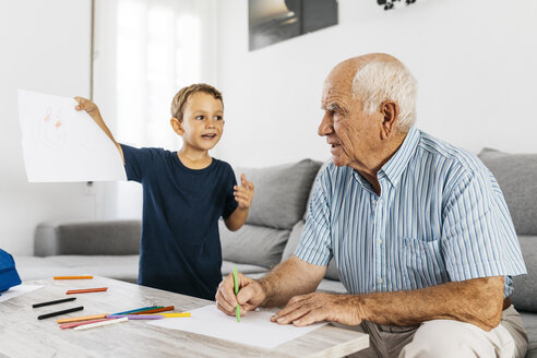 Grandfather and grandson drawing with coloured pencils in the living room - JRFF01818