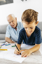 Portrait of little boy drawing with coloured pencils while his grandfather in the background watching him - JRFF01827