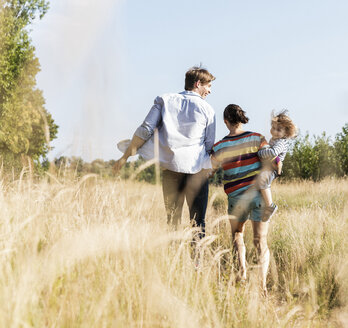 Happy family walking at the riverside on a beautiful summer day - UUF14963