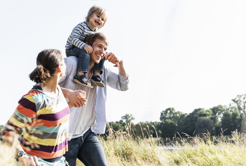 Happy family walking at the riverside on a beautiful summer day - UUF14975