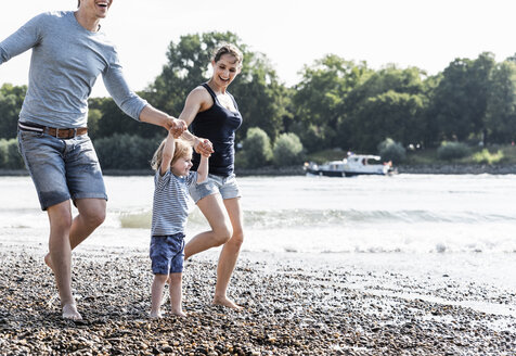 Happy family walking at the riverside on a beautiful summer day - UUF15005