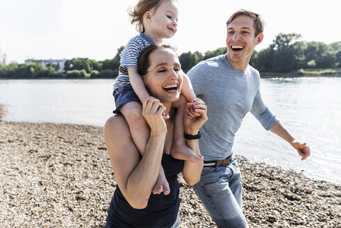 Happy family walking at the riverside on a beautiful summer day - UUF15014