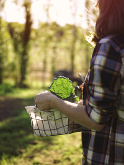 Woman carrying basket of harvested vegetables, partial view - RAMAF00046