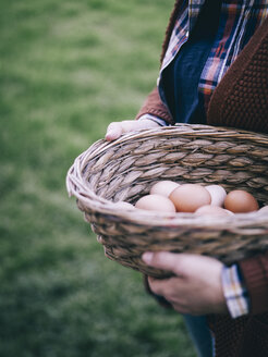 Woman's hands holding basket of fresh brown eggs - RAMAF00055