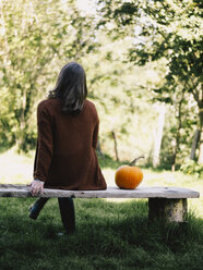 Back view of woman sitting on wooden bench besides a pumpkin - RAMAF00061