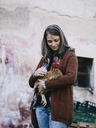 Smiling woman holding chicken on her arm - RAMAF00064