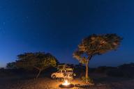 Botswana, Kalahari, Central Kalahari Game Reserve, campsite with campfire under starry sky - FOF10228