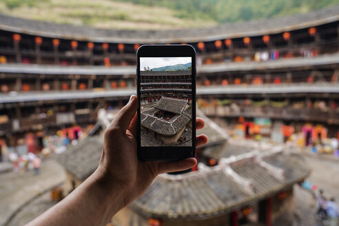 China, Fujian Province, hand taking cell phone picture of the inner courtyard of a tulou in a Hakka village - KKAF01495