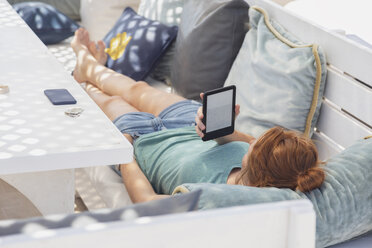 Young woman reading e-book, lying on bench - MMAF00534