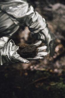 Spaceman exploring nature, holding soil - VPIF00547