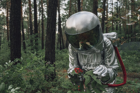 Spaceman exploring nature, examining plants - VPIF00565