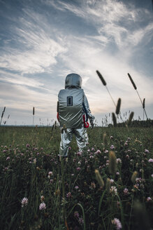 Spaceman exploring nature, standing in meadow, looking at sky - VPIF00583