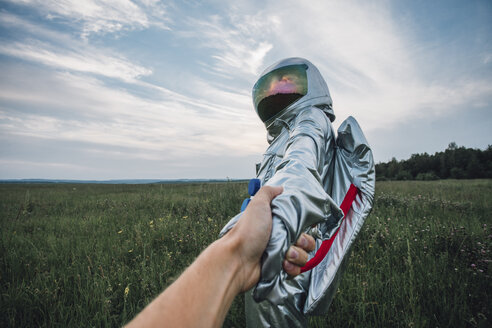 Spaceman exploring nature, holding hands with a human - VPIF00589