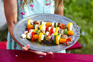 Girl holding plate with vegetarian grill skewers, tomato, yellow and green zucchini, tofu, feta, onion and champignon - SARF03931