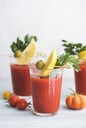 Glasses of fresh spicy tomato juice with cellery garnished with lemon slice, green olive and parsley - IPF00476