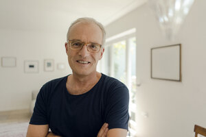 Portrait of a smiling mature man at home - KNSF04596