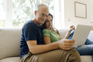 Smiling mature couple sitting on couch at home sharing tablet - KNSF04599