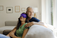 Smiling mature couple sitting on couch at home with woman wearing eye mask - KNSF04602